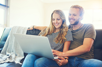 Buy stock photo Shot of a happy young couple using a laptop while relaxing together on the sofa at home