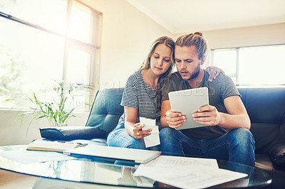 Buy stock photo Shot of a young couple using a digital tablet while going through paperwork at home