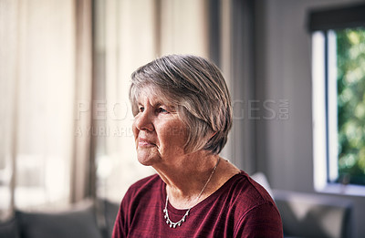 Buy stock photo Cropped shot of an attractive senior woman looking thoughtful while standing in her home alone
