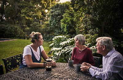 Buy stock photo Cropped shot of a senior couple and their adult daughter enjoying a cup of coffee in the backyard at home home