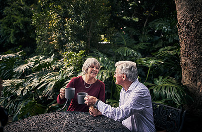 Buy stock photo Cropped shot of an affectionate senior couple enjoying a cup of coffee in their backyard at home