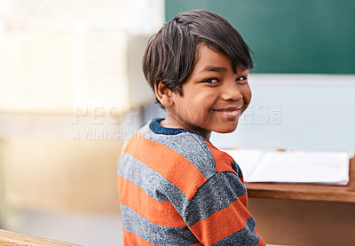 Buy stock photo Portrait of a cheerful young elementary school kid sitting in class during the day