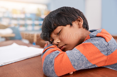 Buy stock photo Cropped shot of a tired elementary school child sleeping on his desk in the classroom