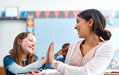 Buy stock photo Shot of a cheerful young female teacher giving her student a high five for doing a great job in the classroom