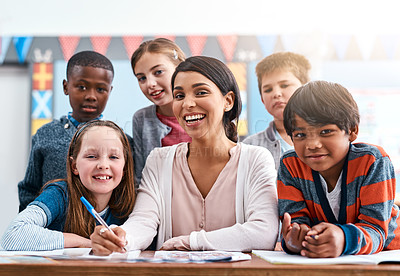 Buy stock photo Portrait of a cheerful young female teacher helping her students inside of the class at school