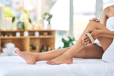 Buy stock photo Shot of a young woman exfoliating her legs with a brush