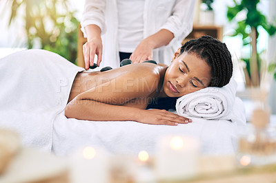 Buy stock photo Shot of an attractive young woman getting a hot stone massage at a spa