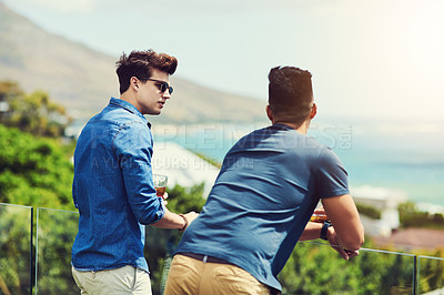 Buy stock photo Rearview shot of two handsome young men having drinks and relaxing outdoors while on holiday