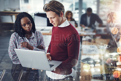Buy stock photo Shot of two young businesspeople using a laptop together with their colleagues working in the background at work