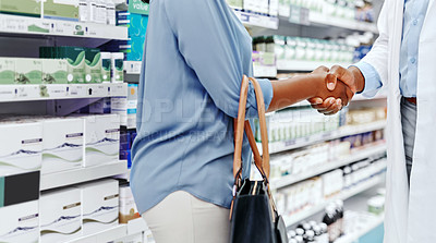 Buy stock photo Closeup shot of a pharmacist and a customer shaking hands in a chemist