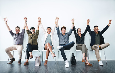 Buy stock photo Studio shot of a group of businesspeople holding hands and cheering in a waiting room