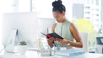 Buy stock photo Shot of an attractive young businesswoman working at her desk in a modern office