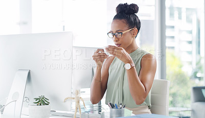 Buy stock photo Shot of an attractive young businesswoman having a cup of coffee while working at her desk in a modern office