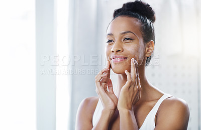 Buy stock photo Shot of an attractive young woman applying moisturizer to her face in the bathroom at home