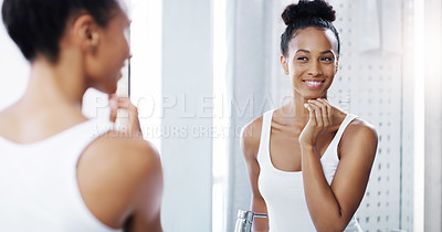 Buy stock photo Shot of an attractive young woman admiring her face in the bathroom at home