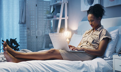Buy stock photo Shot of an attractive young woman using her laptop while lying on her bed after a long day at work