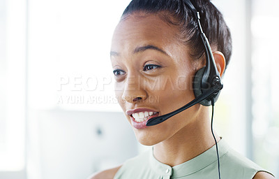Buy stock photo Shot of an attractive young businesswoman wearing headsets while working in her office