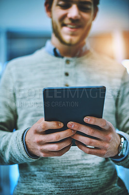 Buy stock photo Shot of a cheerful young businessman using his digital tablet at work