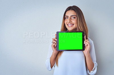 Buy stock photo Portrait of an attractive young woman holding a digital tablet against a blue background