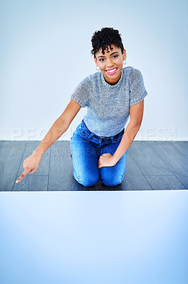 Buy stock photo Full length shot of an attractive young woman kneeling down and pointing her finger downwards against a blue background