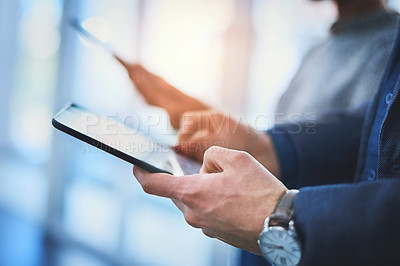 Buy stock photo Closeup shot of two unrecognizable businesspeople using their digital tablets during a meeting at work