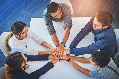 Buy stock photo High angle shot of a group of young businesspeople joining their hands together in unity during a meeting at work