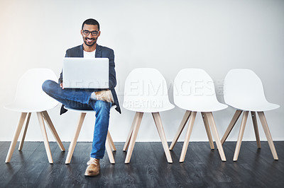 Buy stock photo Full length shot of a handsome young businessman using a laptop while waiting in line