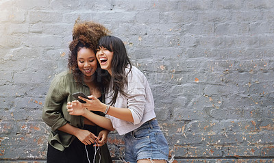Buy stock photo Shot of two cheerful young women using a cellphone together while posing outdoors against a grey brick wall