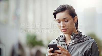 Buy stock photo Shot of an attractive young woman using her cellphone while walking through the city