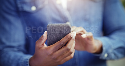 Buy stock photo Shot of an unrecognizable man using his cellphone in the city
