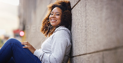 Buy stock photo Portrait of an attractive young woman sitting down and leaning against a building while listening to music in the city