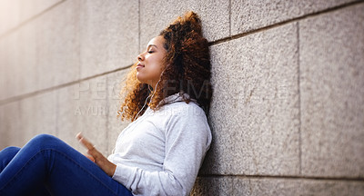 Buy stock photo Shot of an attractive young woman sitting down and leaning against a building while listening to music in the city