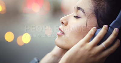 Buy stock photo Closeup shot of an attractive young woman listening to music on her headphones in the city