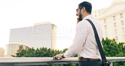 Buy stock photo Shot of a handsome young businessman taking a phone call in the city