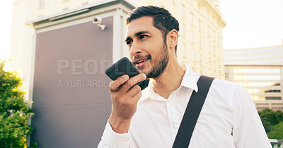 Buy stock photo Shot of a handsome young businessman using his cellphone to make a voice note while walking through the city