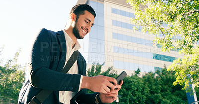 Buy stock photo Shot of a handsome young businessman using his cellphone while commuting to work on his bicycle