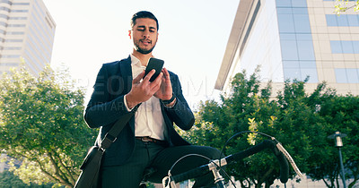 Buy stock photo Low angle shot of a handsome young businessman using his cellphone while commuting to work on his bicycle