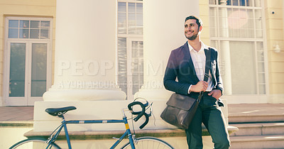 Buy stock photo Shot of a handsome young businessman posing next to a bicycle in the city