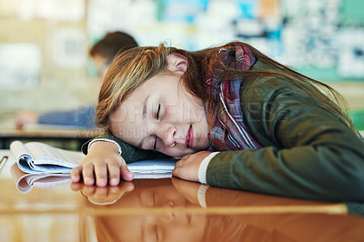 Buy stock photo Shot of an adorable elementary schoolgirl taking a nap on her desk in class