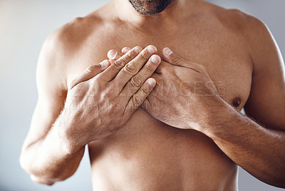 Buy stock photo Shot of a shirtless unrecognizable man holding his chest in pain while relaxing at home