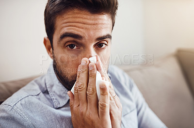 Buy stock photo Portrait of a handsome young man blowing his nose with a tissue while relaxing on a sofa at home