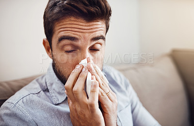 Buy stock photo Shot of a handsome young man blowing his nose with a tissue while relaxing on a sofa at home