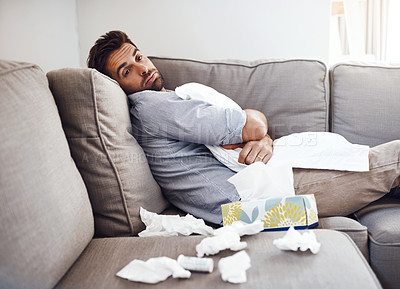 Buy stock photo Portrait of a sickly young man holding a pillow while sitting on a couch with tissues laying all around at home