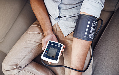 Buy stock photo Closeup shot of an unrecognizable man monitoring his blood pressure levels with a blood pressure monitor at home