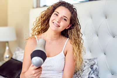 Buy stock photo Portrait of an attractive young woman blowdrying her hair at home