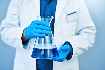 Buy stock photo Studio shot of a scientist holding a beaker against a blue background