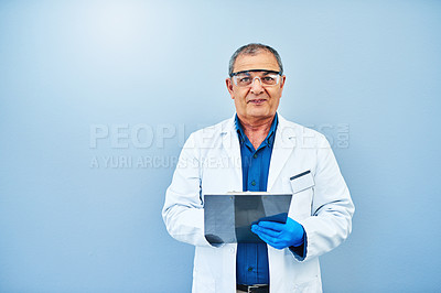 Buy stock photo Studio portrait of a mature scientist writing on a clipboard against a blue background