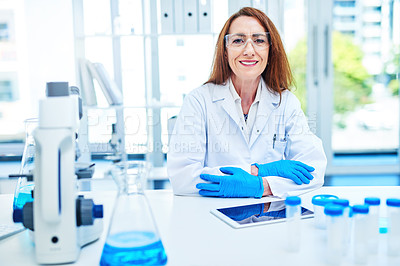 Buy stock photo Portrait of a mature scientist using a digital tablet while working in a laboratory