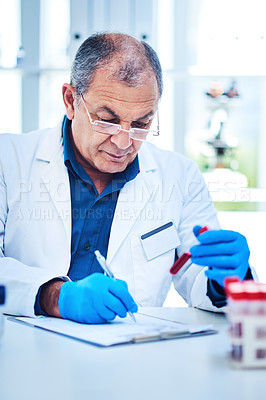 Buy stock photo Shot of a mature scientist writing notes while analyzing samples in a laboratory