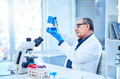 Buy stock photo Shot of a mature scientist conducting an experiment in a laboratory
